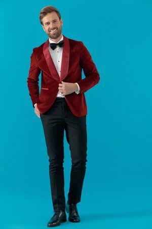 happy elegant fashion man wearing red velvet tuxedo, arranging coat and smiling, walking on blue background, full body