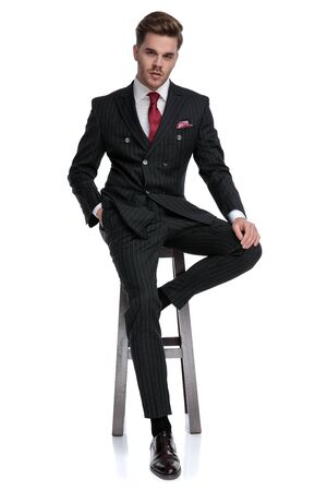 elegant young fashion model wearing double breasted suit and red tie, holding hand in pocket, sitting isolated on white background in studio Stock fotó