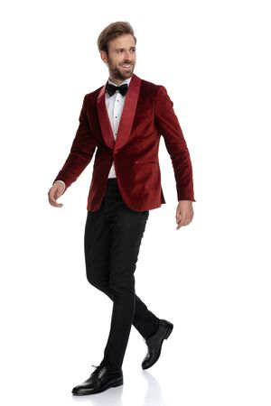 side view of smiling groom wearing red velvet tuxedo, smiling and walking isolated on white background Stock fotó