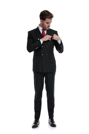elegant young businessman wearing double breasted suit and red tie, arranging handkerchief, standing isolated on white background in studio