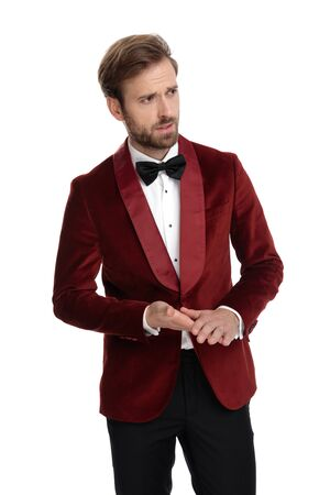 fashion model wearing red velvet tuxedo, touching hands and looking to side, isolated on white background in studio