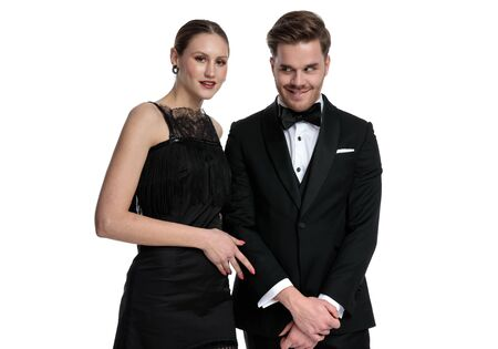 Lovely girlfriend posing beside boyfriend that is making a funny face and wearing a tuxedo, standing on white studio background Stock fotó