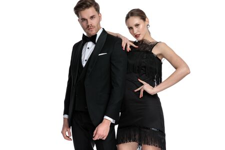 Confident couple posing while she is leaning on him and holding her hand in her whist, wearing a black dress and tuxedo, standing on white studio background Stock fotó