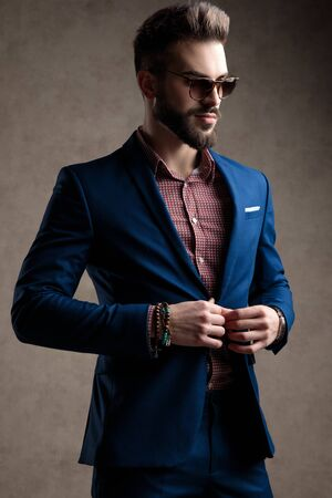 side view of a sexy formal business man wearing a navy suit and sunglasses holding hand on his jackets button while looking ahead confident against gray studio background