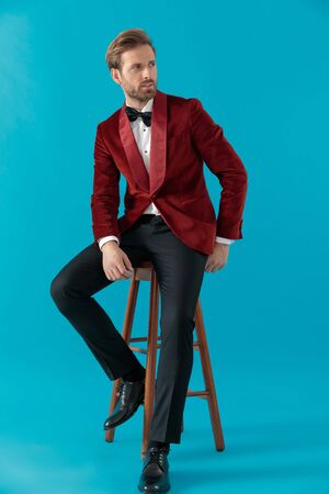 elegant fashion man wearing red velvet tuxedo, holding hands and looking to side, sitting on blue background, full body Stock fotó
