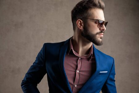 close up of a good looking formal business man wearing a navy suit and sunglasses standing and looking to a side pensive against gray studio background