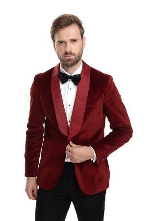 arrogant fashion model wearing red velvet tuxedo, arranging coat and standing isolated on white background in studio