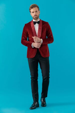 elegant fashion model wearing red velvet tuxedo, arranging shit and walking on blue background, full body