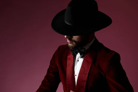 close up of young fashion model wearing red velvet tuxedo and black hat, looking to side and hiding behind hat on pink background in studio