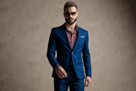 portrait of a charming formal business man wearing a navy suit and sunglasses standing and looking at camera with a powerful attitude against gray studio background