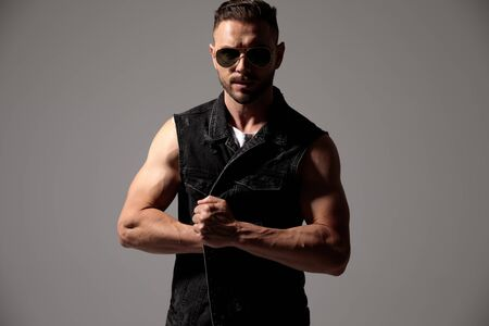 Tough man pulling something out from his black jeans vest while wearing sunglasses and standing on gray studio background Stock fotó
