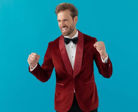 proud elegant man wearing red velvet tuxedo, yelling and celebrating victory, looking to side on blue background Stock fotó