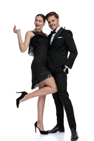 Happy girlfriend posing with her leg in the air beside her boyfriend dressed in a tuxedo and holding his hand in his pocket, standing on white studio background Stock fotó