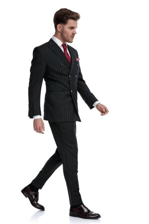 side view of elegant young businessman wearing double breasted suit and brague shoes, walking and looking to side, isolated on white background