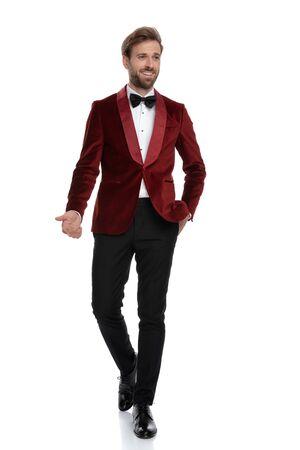 happy groom wearing red velvet tuxedo, smiling and inviting, walking isoalted on white background in studio Stock fotó