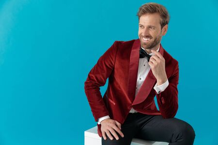 elegant fashion man wearing red velvet tuxedo and smiling, holding hands and looking to side, sitting on blue background