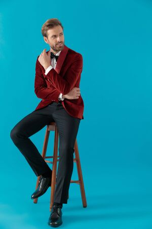 young fashion model wearing red velvet tuxedo and looking to side, holding hands and sitting on blue background, full body Stock fotó