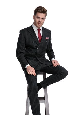 attractive young businessman wearing double breasted suit and red tie, sitting isolated on white background in studio