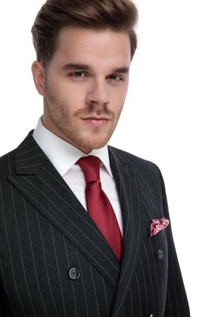 elegant young businessman wearing double breasted suit and red tie, isolated on white background in studio