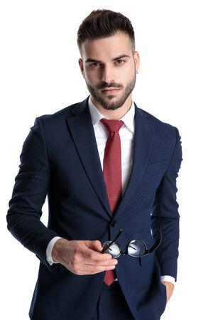 Confident casual businessman holding his glasses and his hand in his pocket while wearing a blue navy suit and standing on white studio background Stock fotó