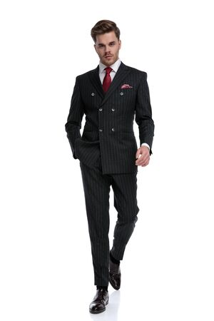 fashion businessman wearing double breasted suit and elegant brogue shoes, walking isolated on white background in studio