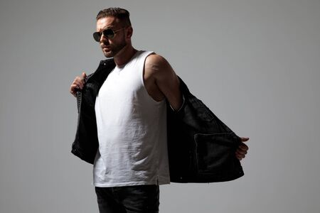 Motivated young man taking off his black jeans vest while wearing sunglasses and looking to the side, standing on gray studio background