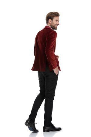 back view of smiling groom wearing red velvet tuxedo and walking, looking to side, isolated on white background in studio