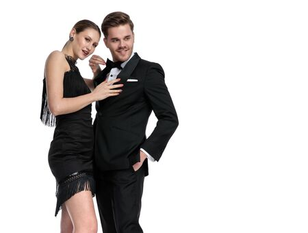 Elegant couple smiling and embracing each other while she is adjusting his jacket and he is looking away and holding his hand in his pocket, wearing a black dress and tuxedo, standing on white studio background