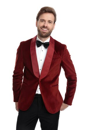 smiling young model wearing red velvet tuxedo, holding hands in pocket, smiling isolated on white background