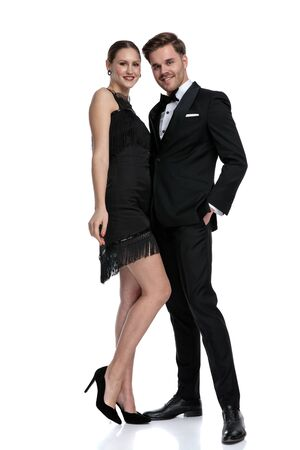 Charming couple smiling and posing facing each other while he is holding his hand in his pocket and wearing a tuxedo, standing on white studio background Stock fotó