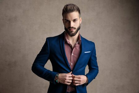 portrait of an attractive formal business man wearing a navy suit standing and fixing his jacket while looking at camera serious against gray studio background Stock fotó
