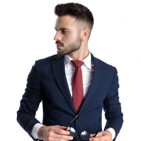 Thoughtful young businessman looking to the side and holding his glasses while wearing a blue navy suit and a red tie, standing on white studio background Stock fotó