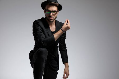 sexy casual man wearing a hat and glasses standing with one leg up and snapping fingers confident against gray studio background