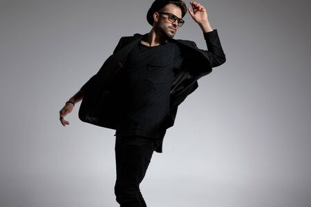 attractive casual man wearing a hat and glasses standing and twisting around while striking a graceful attitude against gray studio background