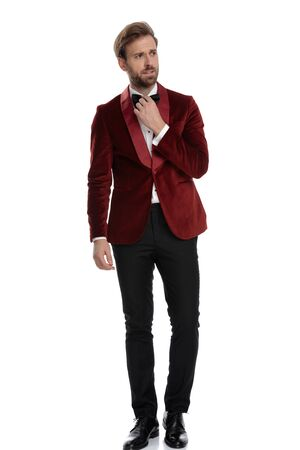 fashion model wearing red velvet tuxedo, fixing bowtie, looking to side and walking, isolated on white background