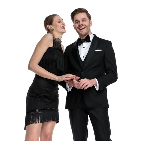 Lovely couple laughing and holding each other's arm while wearing tuxedo and a black dress, standing on white studio background Stock Photo