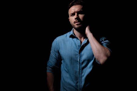 mystérieux homme décontracté portant une chemise bleue debout et révélant son visage de l'ombre tout en touchant son cou pensif sur fond de studio noir Banque d'images