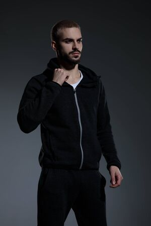 young fashion model wearing gym suit, looking to side and fixing jacket, standing on grey background in studio