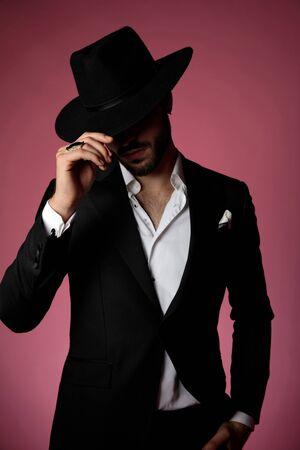 Homme mystérieux saluant et tenant sa main dans sa poche tout en portant un costume noir et un chapeau, debout sur fond de studio couleur cerise