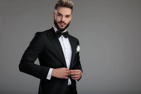 Confident groom unbuttoning his jacket while wearing tuxedo and black bowtie, standing on gray studio background