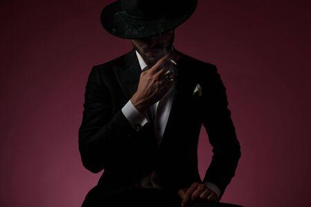 Mächtiger junger Mann, der eine Zigarette raucht und sich auf sein Bein stützt, während er einen schwarzen Anzug und einen Hut trägt und auf kirschfarbenem Studiohintergrund sitzt