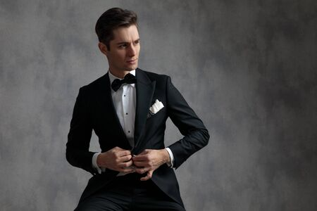 elegant young model in tuxedo arranging coat, looking to side and sitting on grey background in studio