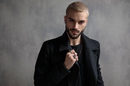 Confident young man adjusting his long black coat and showing his rings while standing on gray wallpaper studio background Stock Photo