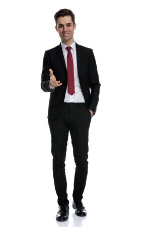 Cheerful businessman giving a handshake and holding his hand in his pocket while wearing a black suit and red tie, walking on white studio background Archivio Fotografico