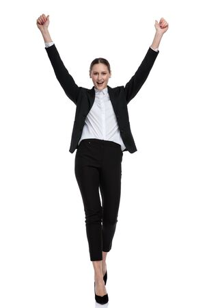 lovely businesswoman wearing black suit walking with hands up in the air against white studio background Stock fotó