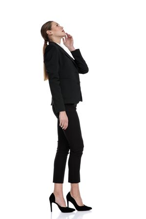 side view of a charming businesswoman waiting in line and looking up thoughtful against white studio background Stock fotó
