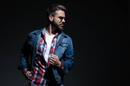 Motivated casual man looking to the side with his fist clenched while wearing sunglasses, jeans jacket and a checkered shirt, standing on black studio background