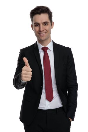 Cheerful businessman giving a thumbs up and holding his hand in his pocket while wearing a black suit and red tie, standing on white studio background