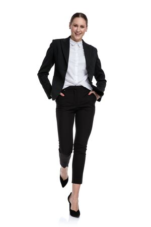 sexy formal businesswoman wearing black suit walking relaxed with hands in pockets and happy against white studio background