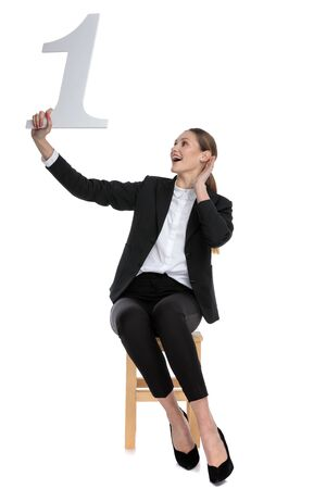 attractive businesswoman wearing black suit sitting and holding a number one with arrogance against white studio background Stock fotó